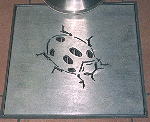 Drain cover at Malivoire Estate with ladybird logo